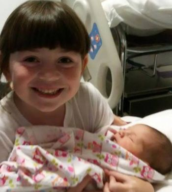Nicole's six-year-old daughter Brooklyn holding baby Scarlett